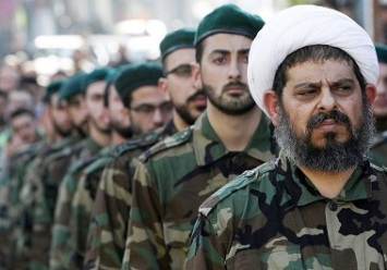 A Shi'ite cleric wearing military uniform stands with Hezbollah members during a funeral for their comrade Abbas Hijazi in Ghaziyeh village
